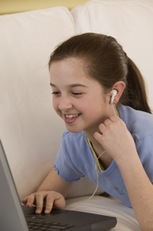 Girl listening to music and using laptop